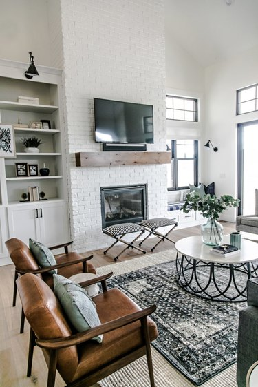 farmhouse living room with layered area rugs, open shelving, and leather lounge chairs