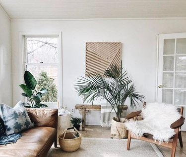 tropical living room with leather sofa and sheepskin fun on lounge chair