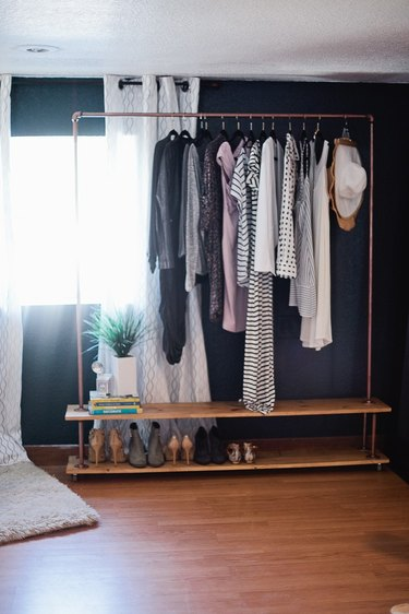 Rolling industrial pipe closet idea in copper with black accent wall