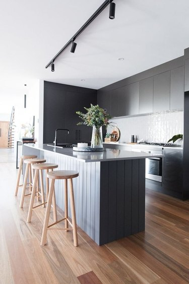 modern kitchen island with black cabinets and wood stools
