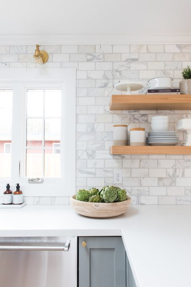 marble subway tile kitchen backsplash with open shelving and gray cabinets