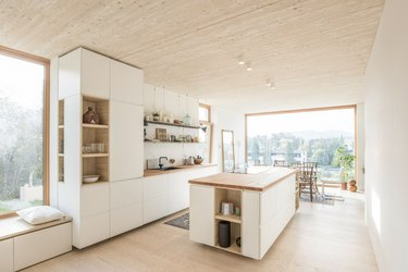 modern kitchen island with white cabinets and wood countertop