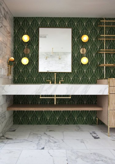 Bathroom with marble vanity, marble floors, green patterned tile wall, brass faucet, sconces, mirror.
