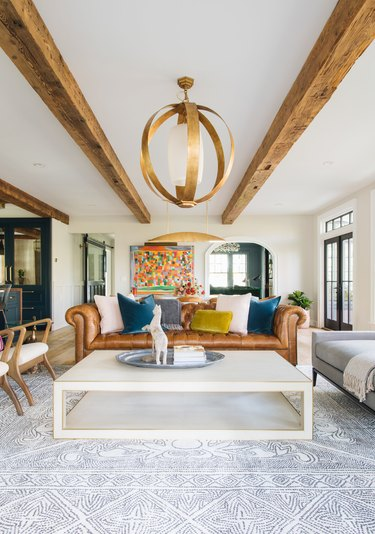 colorful farmhouse living room with wood ceiling beams