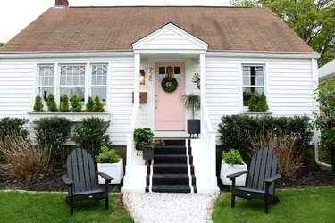 home exterior house color for 2021 in white with pink door and black striped steps