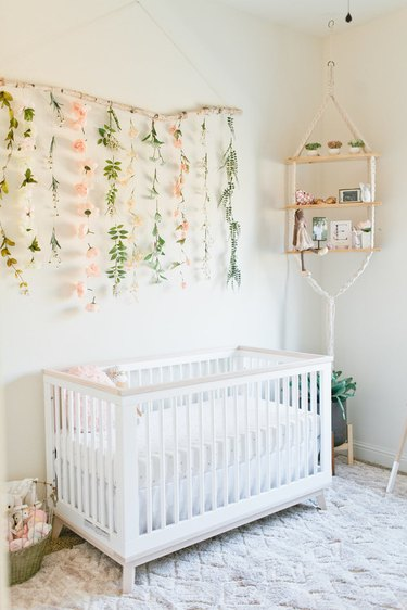 white boho girls nursery with floral wall hanging