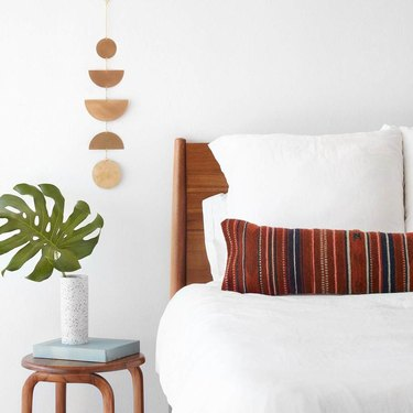 bed with lumbar pillow and plant and wall hanging nearby