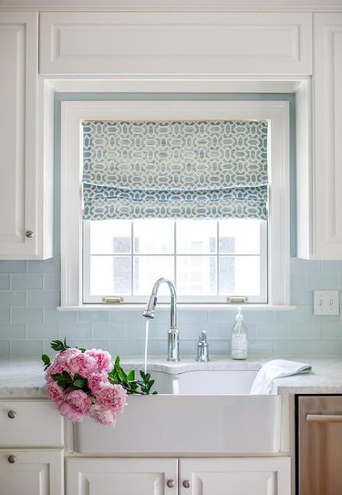 glass subway tile kitchen backsplash with white cabinets and farmhouse sink