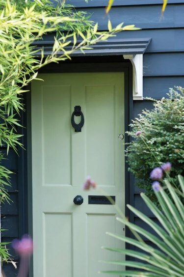 exterior house color for 2021 in dark gray with light green door and landscaping