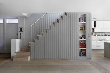 Under the stairs storage with gray paneling and seamless doors