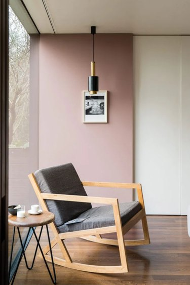 Bauhaus style room with pink accent wall, modern pendant light, and Bauhaus chair