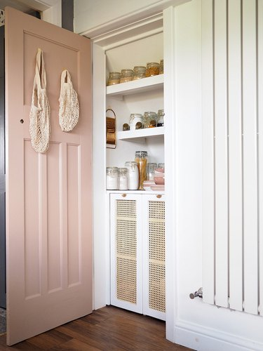Under the stairs storage pantry with pink door and cane cabinets