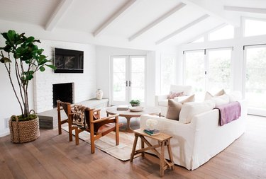 white modern farmhouse with ceiling beams and white brick fireplace surround