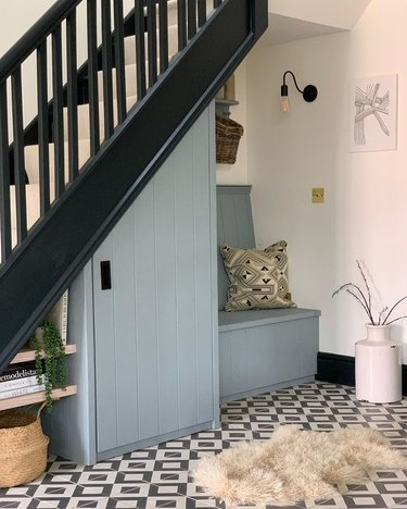 Under the stairs storage with blue painted cupboard and seating