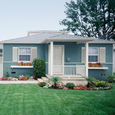 home exterior house color for 2021 in teal with flower boxes and flowers in front yard