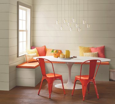 dining room space with banquette and orange chairs