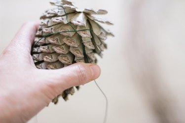 Twisting floral wire around pinecone