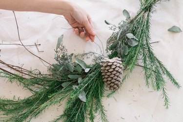 Attaching pinecone to wreath