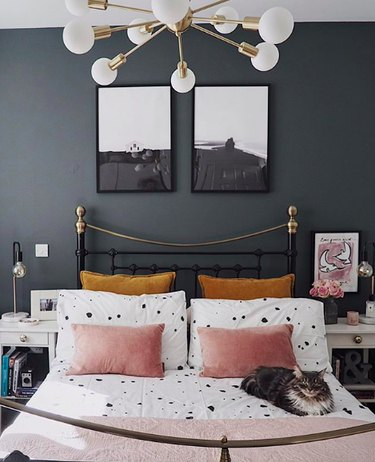 Gray bedroom with white sheets featuring black dot paint spatter and blush and goldenrod velvet pillows. Also featuring brass white globe sputnik chandelier