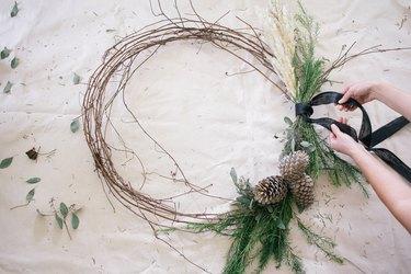Tying ribbon onto wreath