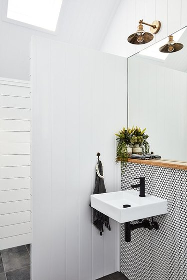 Scandinavian bathroom with white penny tile mosaic and black grout