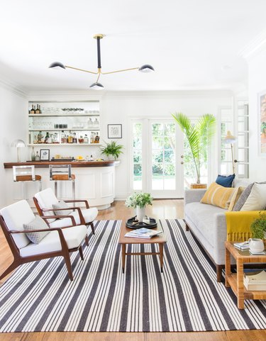 midcentury modern family room by Emily Henderson with midcentury modern chair set and mini bar.