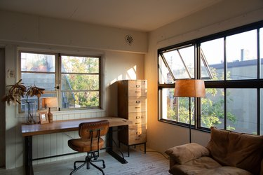 home office in living room idea with desk in front of large windows