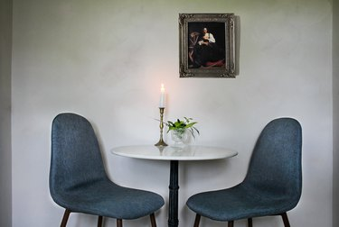 small dining room area with green chairs and a candle.