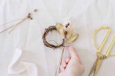 Tying floral bundle to mini grapevine wreath