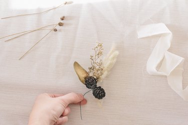 Tying pinecones to floral stems