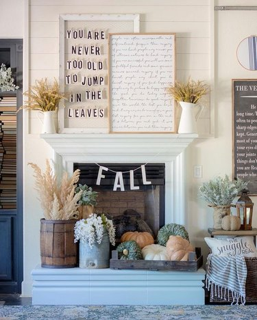 fall-inspired mantel decor with seasonal signage and pumpkins