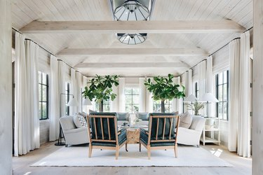 neutral living room with pitched ceiling and drapery