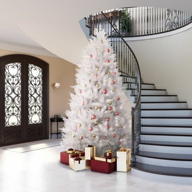 White Christmas Tree Ideas with White artificial Christmas tree, red and gold ball ornaments, sloped staircase, double entry doors, white floors, foyer.