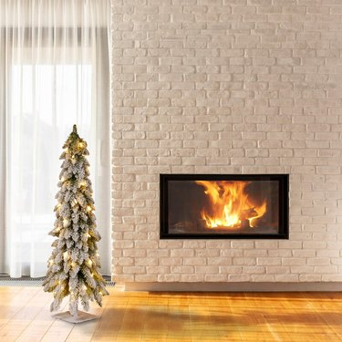 White Christmas Tree Ideas with Artificial white flocked Christmas tree with white brick fireplace.