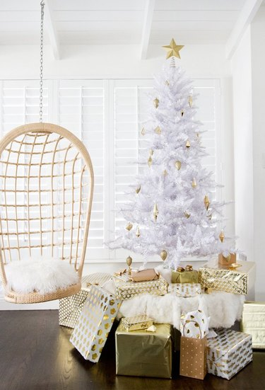 White Christmas Tree Ideas with White artificial Christmas tree decorated with gold ornaments and gold wrapped presents, hanging cane chair, white shutters.