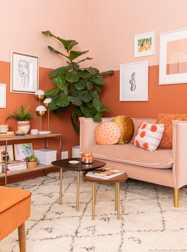warm colors in living room with orange and pink walls and neutral rug