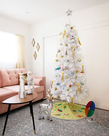 White Christmas Tree Ideas with White artificial Christmas tree with mod ornaments and skirt, pink couch, mod coffee table, mod floor tiles, white walls.