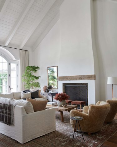 Living room with couch, chairs, coffee table, large farmhouse fireplace, vintage rug.