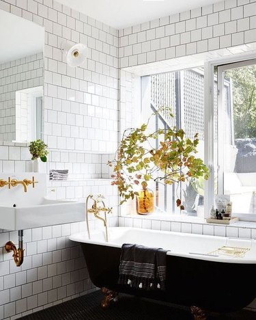 black clawfoot bathtub with brass fixtures and white subway tile