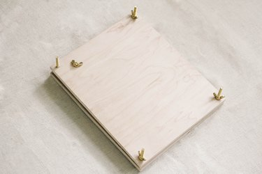Brass bolts and wing nuts attached to wood boards of flower press