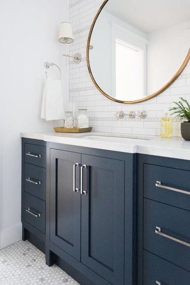 bathroom idea with blue cabinets and white countertop