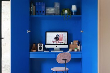 cobalt blue home office tucked in a closet with desk and shelving