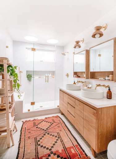 bathroom idea with rug and wood vanity cabinet next to walk-in shower