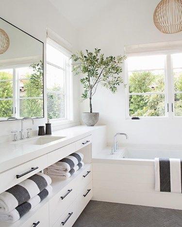 bathroom idea with towel storage in vanity cabinet and pendant hanging over bathtub near windows