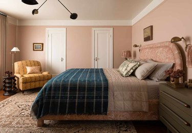 pink bedroom color idea with ochre chair and pink bed with navy throw