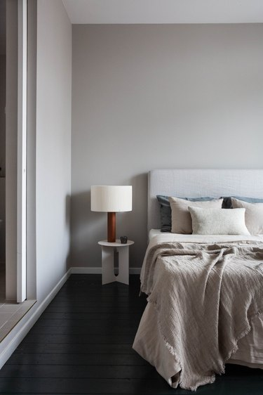 gray bedroom color idea with dark wood flooring