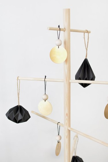 minimalist brass-colored ornaments on a wooden tree stand