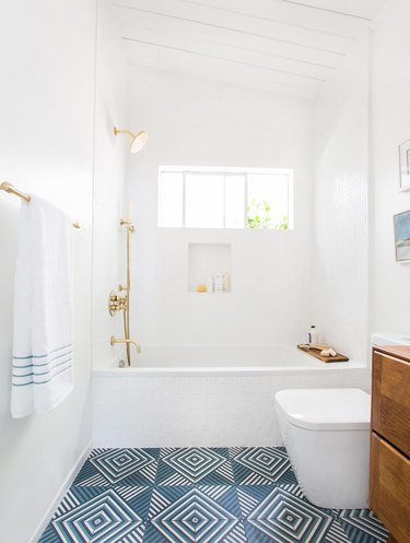 bathroom idea with brass bathroom fittings and patterned floor tile with wood vanity