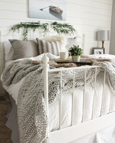 farmhouse bedroom with shiplap walls and layered bedding