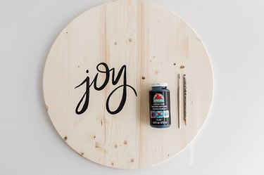 """Paint the word """"joy"""" on the face of your wooden circle."""